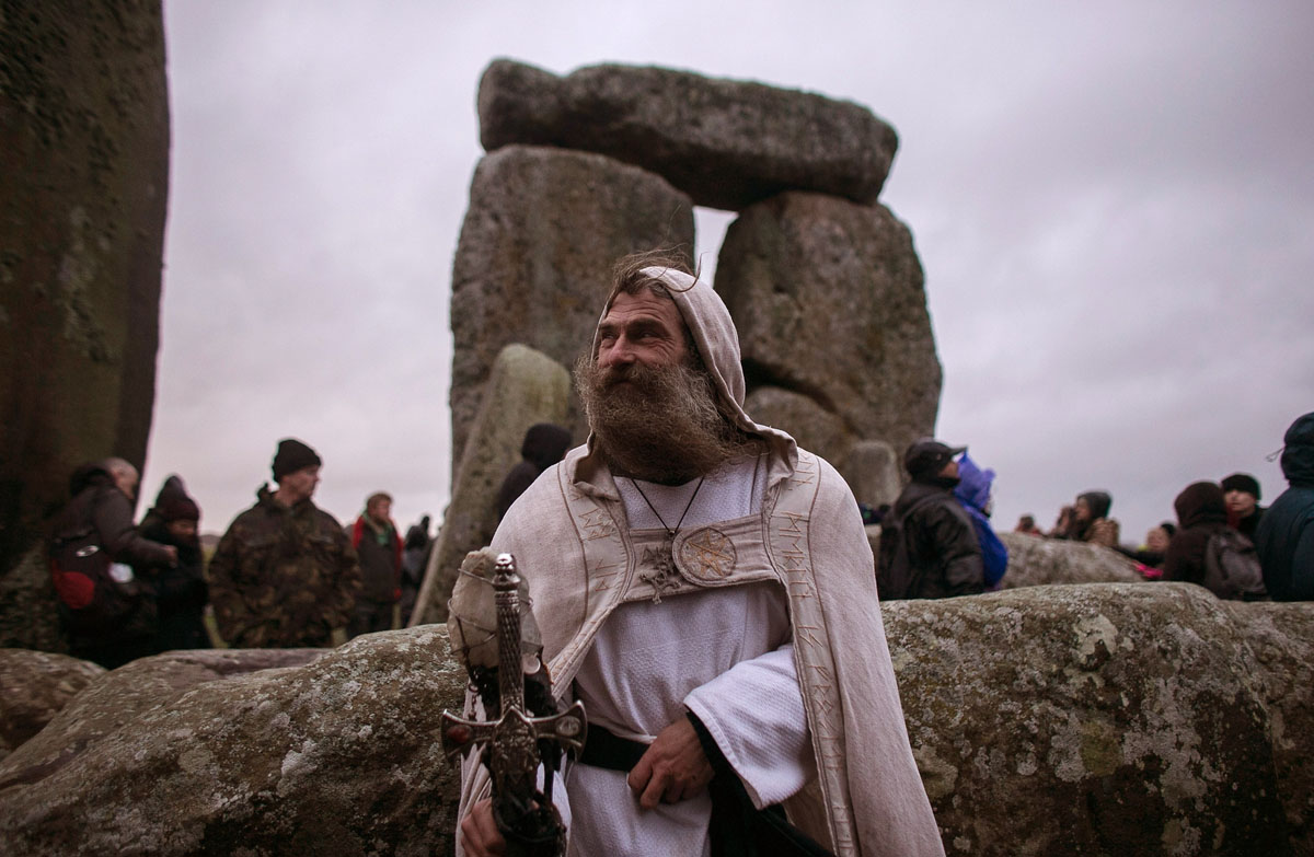 WILTSHIRE, ENGLAND - DECEMBER 21: Druid Merlin  poses for a photograph as druids, pagans and revellers gather, hoping to see the sun rise as they take part in a winter solstice ceremony at Stonehenge on December 21, 2013 in Wiltshire, England. Despite the rain and wind, a large crowd gathered at the famous historic stone circle to celebrate the sunrise closest to the Winter Solstice, the shortest day of the year - an event claimed to be more important in the pagan calendar than the summer solstice, because it marks the 're-birth' of the Sun for the New Year.  (Photo by Matt Cardy/Getty Images) ORG XMIT: 459369497