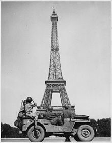 220px-WWII,_Europe,_France,_American_soldiers_watch_as_the_Tricolor_flies_from_the_Eiffel_Tower_again_-_NARA_-_196289